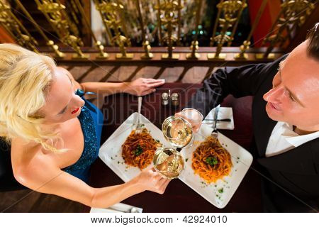 happy couple have a romantic date in a fine dining restaurant they drink wine and clinking glasses, cheers