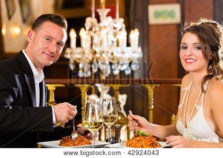 glückliches Paar-habe-ein romantisches Date in einem feinen Gläser Speiserestaurant, sie trinken Wein und klirrend,
