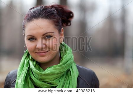 Portrait girl in a green scarf in the park