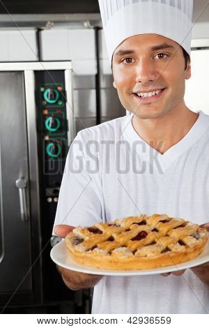 Portrait of happy young chef presenting sweet dish in industrial kitchen