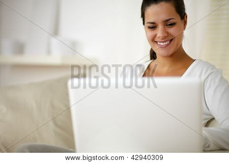 Young Woman Sitting On Couch And Working On Laptop