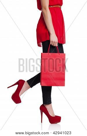 Low section of woman holding red shopping bag