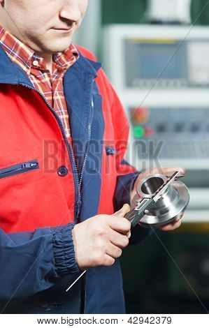 mechanical technician worker measuring detail tool befor processing on cutting machine center at workshop