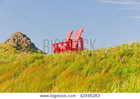Red Chairs Against A Blue Sky