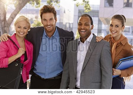 Portrait of happy businessteam standing hugging outdoors, looking at camera.