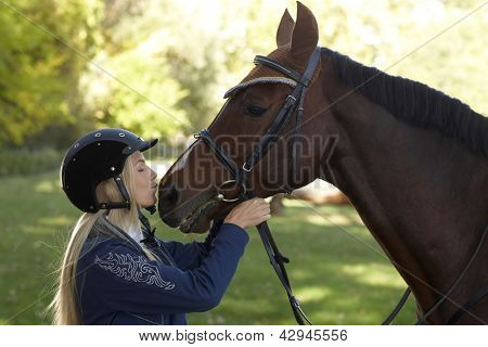 Female rider kissing horse, outdoor photo. Friendship between rider and horse.