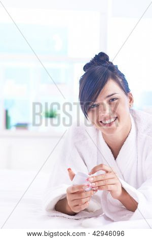 Girl with cream in hands looking at camera