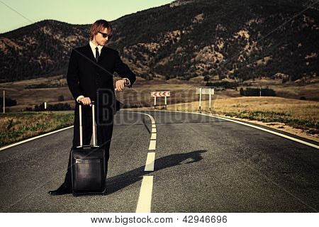 Handsome business man standing on a highway with his suitcase and looking at his watch.