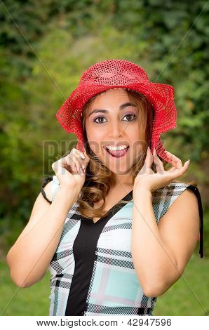 Cheerful woman, straw hat surprised at park
