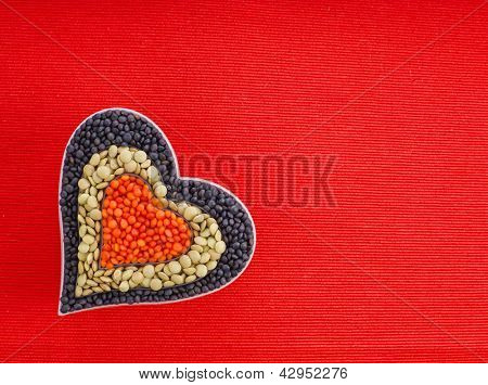 different types of grains of lentils in the shape heart on red canvas background