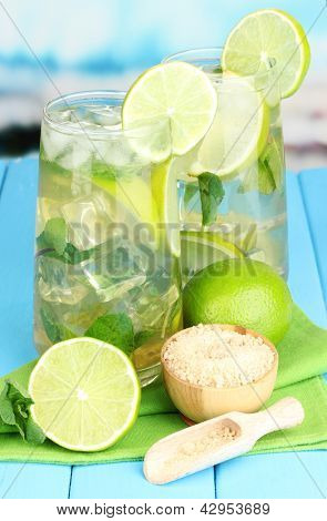 Glasses of cocktail with lime and mint on blue wooden table on bright background