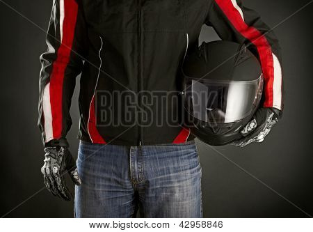 Biker with helmet in his hands. Dark background