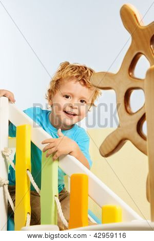 Happy Kid Sitting On The Playground Stairs