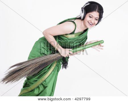 Frau indischen Ursprungs halten einen Besen und Gesang