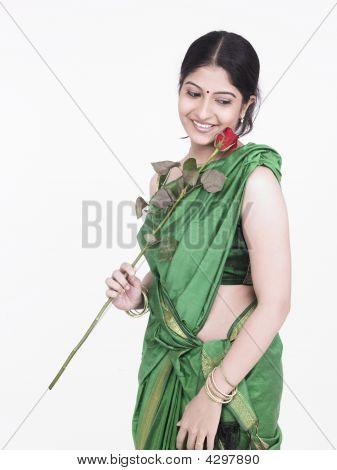 Frau indischen Ursprungs hält eine einzelne Rose