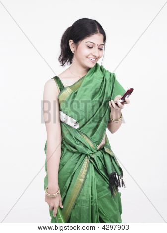 Beautiful Young Asian Woman Of Indian Origin Holding A Cell Phone In One Hand, A Newspaper Rolled An