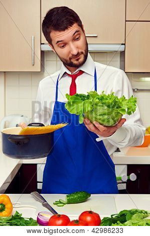 amazed man holding lettuce and pan with spaghetti at the kitchen