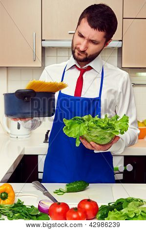 pensive man in blue apron holding lettuce and pan with spaghetti