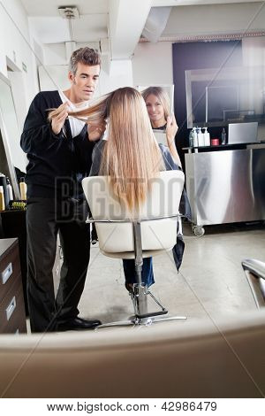 Female client holding mirror while hairdresser styling her hair at parlor