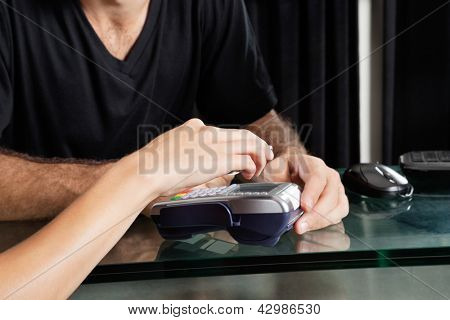 Young female customer paying with mobilephone over electronic reader at salon