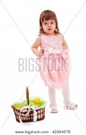 little girl  standing near basket