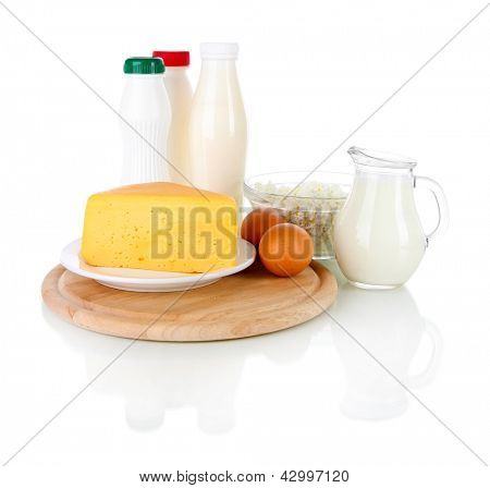 Dairy products and eggs on cutting board isolated on white
