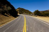stock photo of veer  - An remote mountainside road looking uphill veering left - JPG
