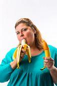 Постер, плакат: Молодая женщина держащая два бананы в руке презерватив pulled над одной есть еще один банан