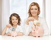 stock photo of pre-teens  - mother and daughter with piggy banks and paper money - JPG