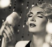 Monochrome portrait of elegant blond retro woman singer with beautiful hairdo