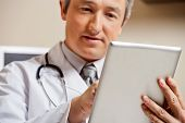 stock photo of maturity  - Close up of mature male doctor using digital tablet - JPG