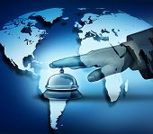 picture of first class  - Global hotel service concept with a human hand ringing a bell on a blue world map background as a hotel symbol of first class international hospitality service - JPG