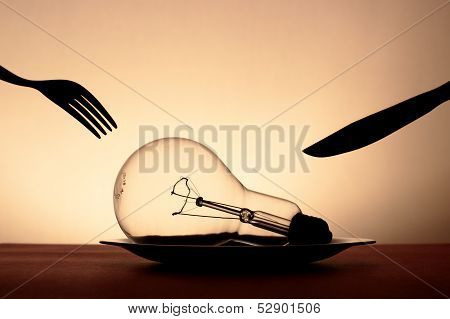 Big Light Bulb In Plate And Cutlery Hovering Over It