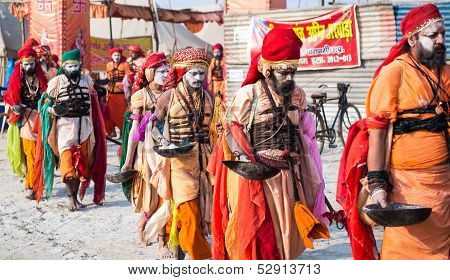 Group of unidentified indian sadhu (holy man) walk on a street  during celebration Kumbha Mela