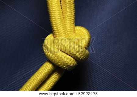 Gordian Yellow Knot On Blue Fabric Background