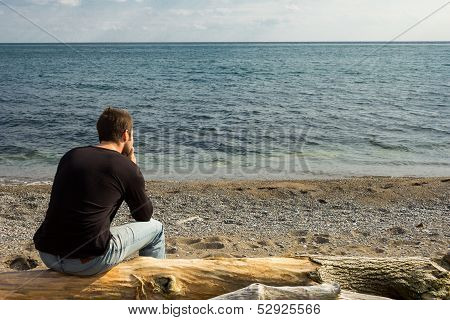 Man thinking on a log