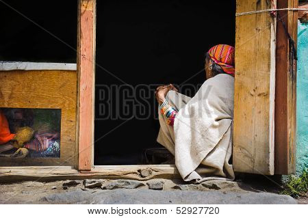 Indian Woman Sitting In Front Of Her House