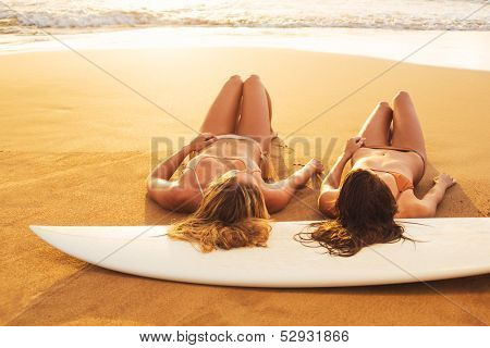 Beautiful Surfer Girls on the Beach at Sunset