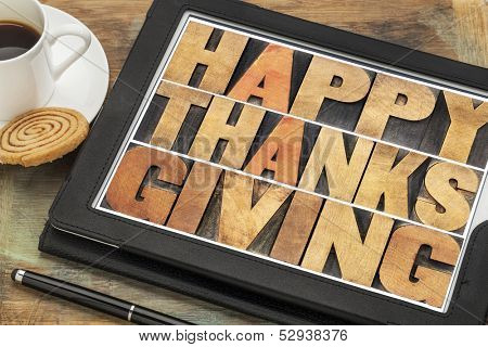 Happy Thanksgiving in letterpress wood type on digital tablet computer with stylus pen, coffee cup and cookie
