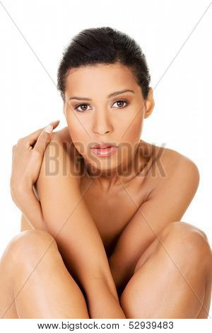 Beautiful and naked women sitting and covering her nudity by her legs and arms. Front view. . Isolated on white.