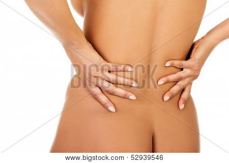 Woman holding her lower back, feeling spine ache in a close up. Isolated on white.