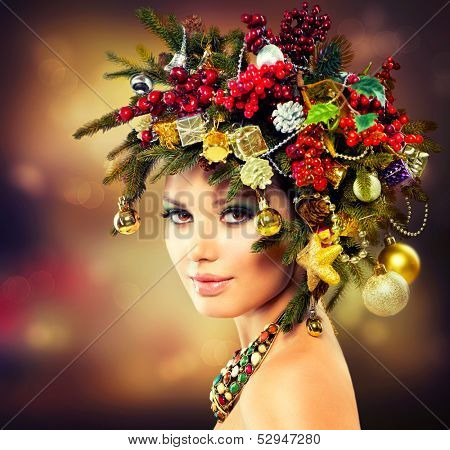 Christmas Winter Woman. Beautiful New Year and Christmas Tree Holiday Hairstyle and Make up. Beauty Fashion Model Girl over Holiday Blinking Background. Creative  Hair style decorated with Baubles