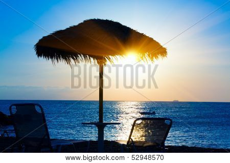 Beach umbrella on the beach at sunset, Santorini Greece
