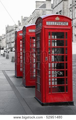 A row of classic British phone boxes on The Royal Mile, Edinburgh, Scotland. Retro effect in black and white with red