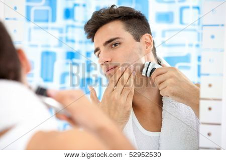 Young man shaving by electric shaver