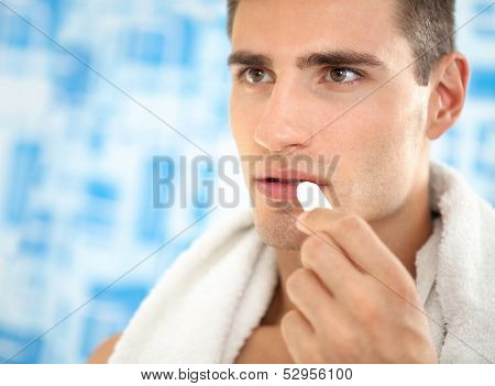 Handsome  man  applying balsam for lips, care of  lips