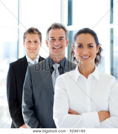 Mature Businessman Smiling At The Camera In A Line