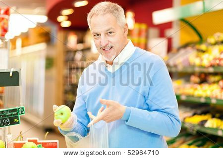 Man buying an apple in a supermarket