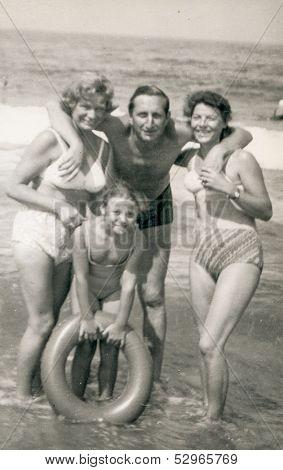SOPOT, POLAND - CIRCA 1950: Vintage photo of man, two women and a girl with lifebuoy on beach, Sopot, Poland, circa 1950.