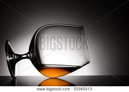 A brandy snifter laying on it side. Horizontal format with a light to dark gray spot background.
